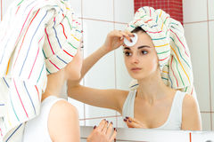 Young girl with towel on the hair looks in the mirror and dabbing makeup from the face. Close-up Stock Photo