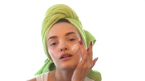 Young girl with a towel on head gently causing the cream on her face stock video footage