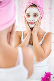 Young girl  with a towel on her head and  cosmetic mask Royalty Free Stock Photography