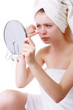 Young girl in a towel on his head, sees his face in the mirror. Stock Photography