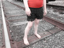 Young Girl On Train Tracks. Young barefoot girl on train tracks stock images