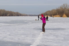 Young girl training new element of skating on a frozen river Royalty Free Stock Photo