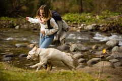 Young girl trains and plays with puppy golden retriever in the wild, next to a river. royalty free stock photo