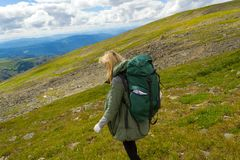 Young girl travel with big green backpack go down the hill on the rocks towards the green fields in altai mountains named sarlyk, royalty free stock photos