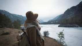 A young girl traveler approaches the edge of the cliff shore. He looks out into the distance to the frozen river in. Winter. A hat and a traveler`s backpack are stock video