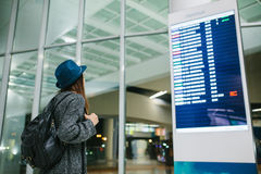 Young girl traveler with a backpack in a hat looks at the information board at the airport. Getting information about Stock Image