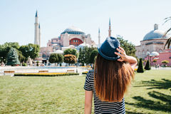 A young girl traveler in a hat from the back in Sultanahmet Square next to the famous Aya Sofia mosque in Istanbul Stock Image
