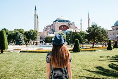 A young girl traveler in a hat from the back in Sultanahmet Square next to the famous Aya Sofia mosque in Istanbul. Turkey. Travel, tourism Royalty Free Stock Photos