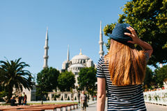 A young girl traveler in a hat from the back in Sultanahmet Square next to the famous mosque called the Blue Mosque in Royalty Free Stock Photos