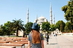 A young girl traveler in a hat from the back in Sultanahmet Square next to the famous mosque called the Blue Mosque in. Istanbul, Turkey. Travel, tourism Stock Images