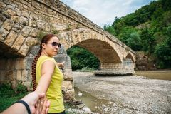 Young girl traveler leads man by hand to ancient bridge royalty free stock photo