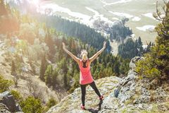 Young girl traveler stands on top of the mountain with arms outstretched.. The girl loves to travel. Concept for stock photography