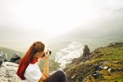 A young girl traveler takes pictures of a summer mountain landscape. Elbrus region, Russia. Woman Emancipation Concept royalty free stock photography