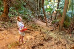A young girl traveler in white stands in the tropical jungle and is going to go on. Around the palm trees and thickets, highlands.  royalty free stock photography