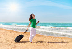 Young girl with traveling bag. Young happy girl with traveling bag walking on the beach stock photo