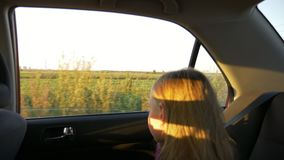 Young girl traveling by car summer evening. Rural scene at window. Focus to background. Unfocused girl close up handheld. Shot stock video
