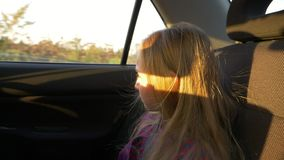 Young girl traveling by car summer evening. Rural scene at window. Girl close up handheld shot. Young girl traveling by car summer evening. Rural scene at stock video footage