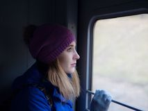 A young girl is traveling on a train. stock photography