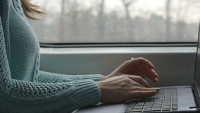 Young girl traveling in a train and using notebook. Female hands typing on keyboard of laptop during riding on railroad stock footage