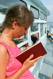 Young girl is traveling on white ship and reading book. Royalty Free Stock Photos