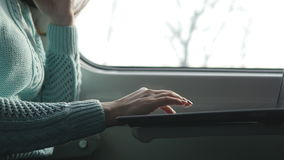 Young girl travelling in a train and using notebook. Female hands using touchpad of laptop pc. Girl chatting with stock footage