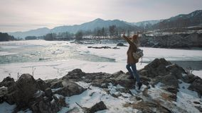 A young girl travels to a frozen river and raises her hands up. Enjoys life, enjoys traveling. A young girl travels to a frozen river and raises her hands up stock footage