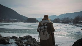 A young girl travels to a frozen river and raises her hands up. Enjoys life, enjoys traveling. A young girl travels to a frozen river and raises her hands up stock video footage