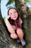 Young girl in tree. Young girl sitting on trunks of huge oak trees Stock Image