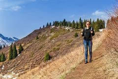 Young girl with trekking sticks walks along the mountain trail. Tourism. Healthy lifestyle Stock Images