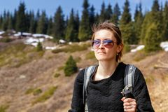 Young girl with trekking sticks walks along the mountain trail. Healthy lifestyle Stock Photos