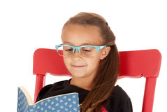 Young girl in trendy blue glasses reading a book Stock Images