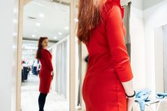 Young girl tries on a red dress in a fitting room boutique. woman buys clothes in the store royalty free stock photography