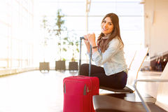 Young girl with trolly bag in airport Stock Photography