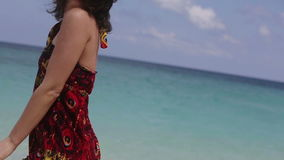 Young girl on tropical beach. Young girl posing for a photograph on a tropical beach.Behind the blue sea, blue sky with clouds, she smiles stock video footage