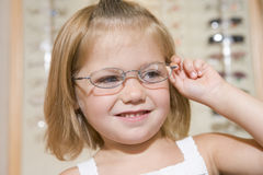 Young girl trying on eyeglasses at optometrists. Smiling Royalty Free Stock Images