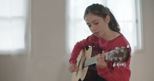 Young girl trying to play guitar, having problems. Young girl having trouble playing the guitar stock video