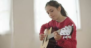 Young girl trying to play guitar, having problems. Young girl having trouble playing the guitar stock video footage