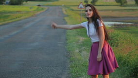 Young girl trying to stop car on road. Hitchhiking attractive woman with thumb up stock footage