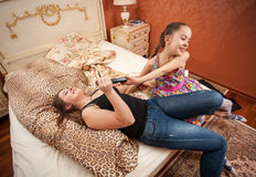 Young girl trying to take TV remote from adult sister Royalty Free Stock Image