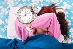 Young girl trying to throw the alarm clock Royalty Free Stock Photos