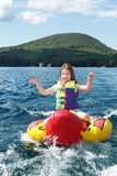 Young girl tubing behind a boat Royalty Free Stock Photos