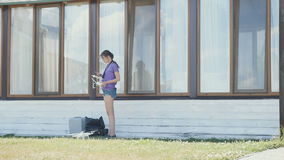 Young girl tune up the drone before flying. Young girl stands near the house in shadow. Beautiful girl holds a telephone in hands and tune up the drone before stock video footage