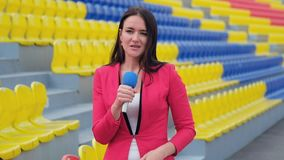 Young girl TV reporter is broadcasting. From stadium stock video footage