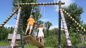 Young girl and two boys  swinging high stock video