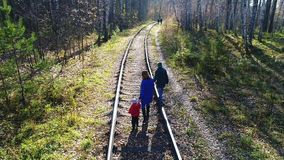 A young girl with two children walking on the railroad. A walk outdoors in the fall. A young girl with two children walking on the railroad. A walk outdoors stock footage