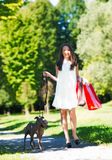 Young girl  with two greyhounds in the park with shopping bags Stock Image