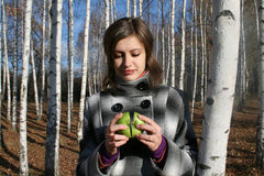 Young girl with two halves of an apple. The young girl in a checkered coat with two halves of a green apple stock photos
