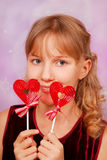 Young girl with two heart shape lollipops Stock Photos