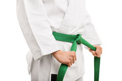 Young girl tying her karate belt Royalty Free Stock Photos
