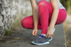 Young girl tying shoelaces on cross-country sneakers outdoors. Stock Images
